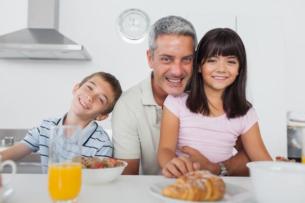 Irmãos tomando café da manhã na cozinha junto com o pai