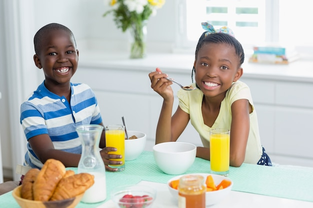 Irmãos tomando café na mesa de jantar em casa