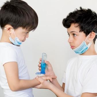 Irmãos usando desinfetante para as mãos