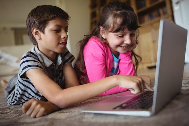 Irmãos usando laptop na sala de estar