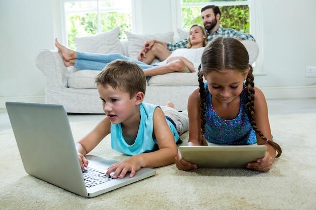 Irmãos usando tecnologias contra pais relaxando no sofá