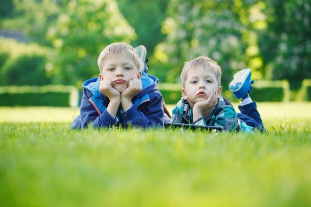 Irmãos, usando, um, tabuleta, yingon, capim, parque, em, suny, dia