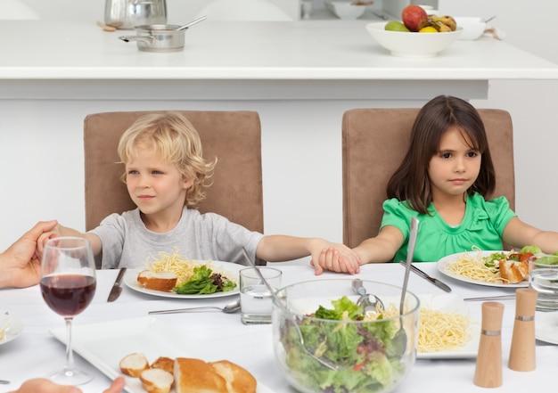 Irmãozinho e irmã segurando as mãos enquanto rezam no almoço