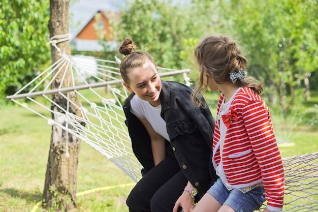 Irmãs adolescentes e criança se divertindo em uma rede no jardim do quintal