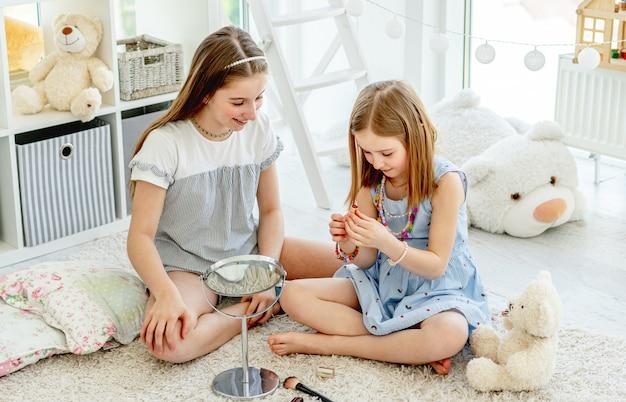 Irmãs alegres brincando com cosméticos