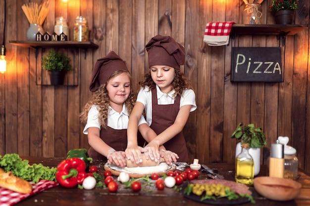 Irmãs alegres que cozinham pizza juntos
