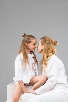 Irmãs amáveis e agradáveis estando perto umas das outras e narizes engraçados esfregando
