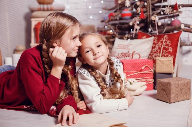 Irmãs amigas se abraçando, sentadas à árvore de natal, o conceito de infância, o natal