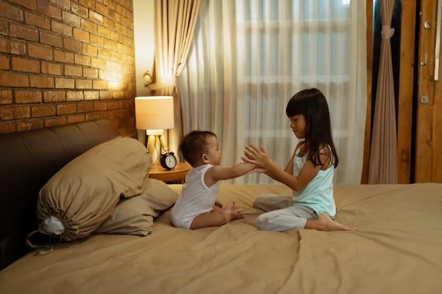 Irmãs asiáticas brincando na cama