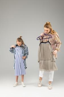 Irmãs atenciosas e bonitas, juntas, experimentando novos vestidos festivos