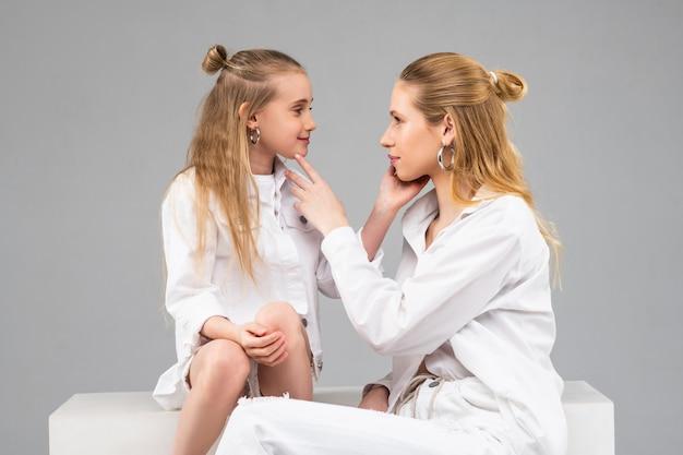 Irmãs bonitas de cabelos compridos em roupas brancas, tocando suavemente o rosto uma da outra e olhando atentamente