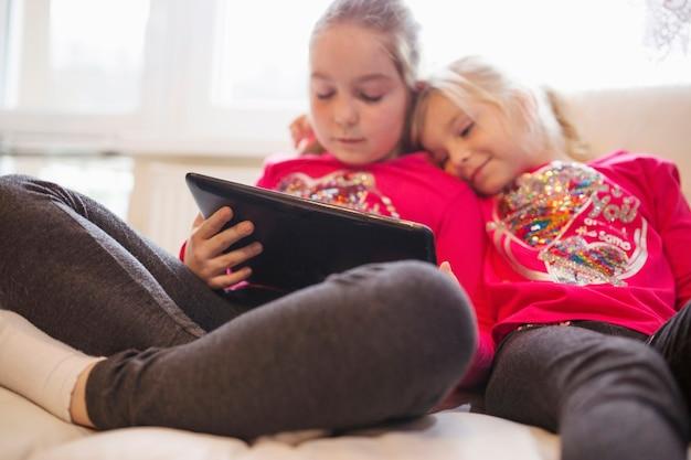 Irmãs bonitos assistindo vídeo no tablet