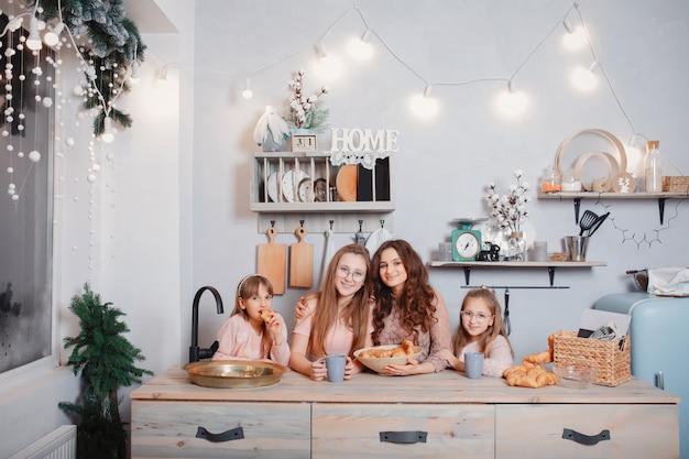 Irmãs bonitos em pé em uma cozinha e come pães