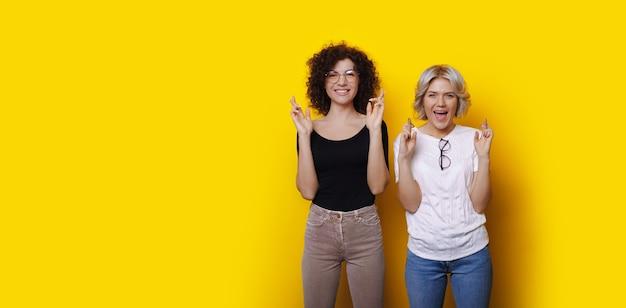 Irmãs brancas com cabelos cacheados sonhando com algo na parede amarela de um estúdio com espaço livre