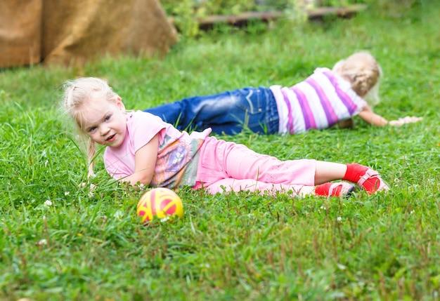 Irmãs brincando na campina com bola