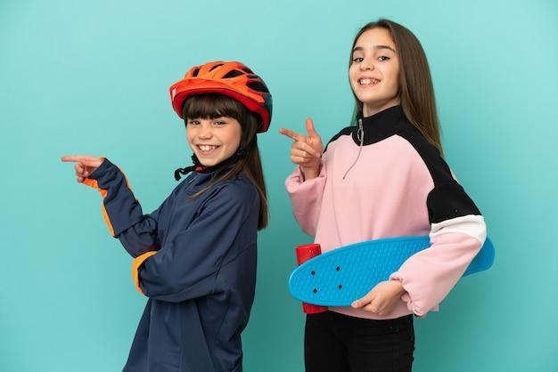 Irmãs caçulas praticando ciclismo e patinadora isoladas em um fundo azul apontando o dedo para o lado na posição lateral