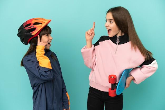 Irmãs caçulas praticando ciclismo e skatista isoladas em um fundo azul com a intenção de descobrir a solução enquanto levantam um dedo