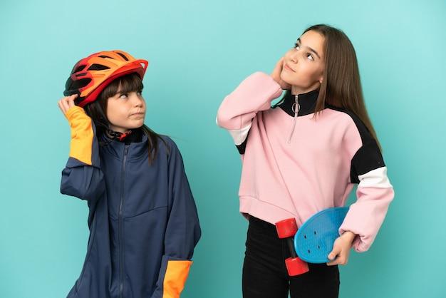 Irmãs caçulas praticando ciclismo e skatista isoladas em um fundo azul pensando em uma ideia enquanto coçam a cabeça