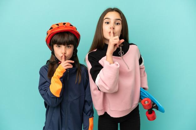 Irmãs caçulas praticando ciclismo e skatista isoladas mostrando um sinal de silêncio gesto colocando o dedo na boca