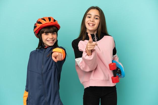 Irmãs caçulas praticando ciclismo e skatistas apontam o dedo para você com uma expressão confiante
