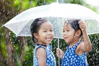 Irmãs com guarda-chuva se divertindo brincando na chuva
