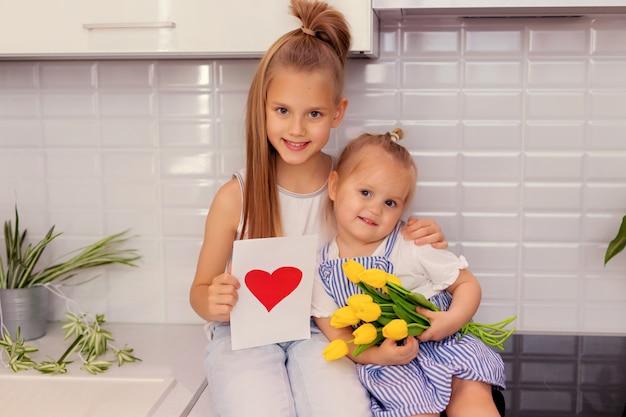 Irmãs com um buquê de flores e um cartão postal na cozinha. dia dos pais.