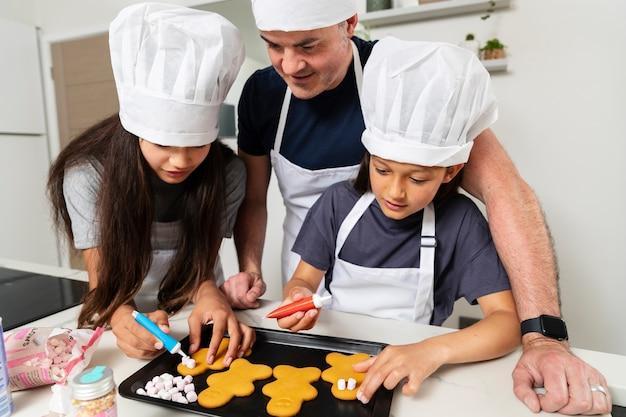 Irmãs cozinhando na cozinha com o pai