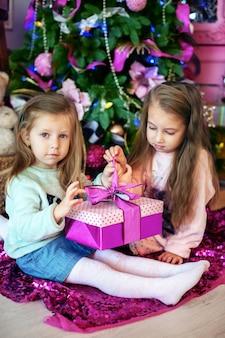 Irmãs, crianças segurando presentes.