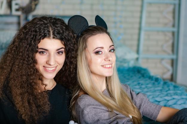Irmãs de cabelo preto e cabelos louros sentar em uma manta de malha azul juntos na cama.