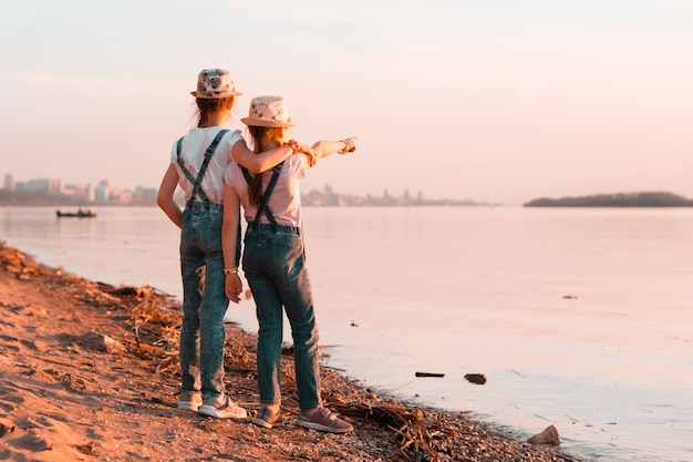 Irmãs de duas meninas ficam nas margens do rio ao pôr do sol e olham para a distância.