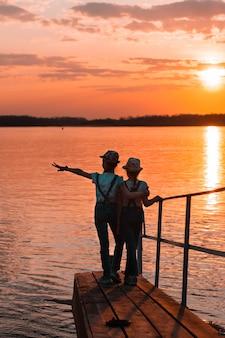 Irmãs de duas meninas ficar em uma ponte de madeira perto da margem do rio ao pôr do sol e olhar para a distância.