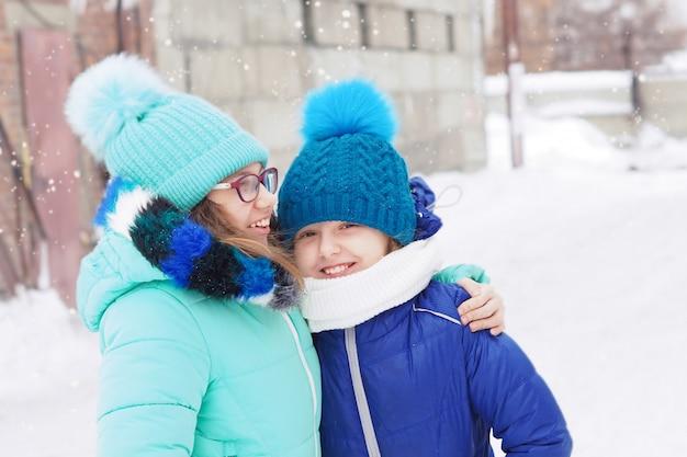 Irmãs de duas meninas no inverno nas ruas em jaquetas e chapéus riem e abraçam. nevando.