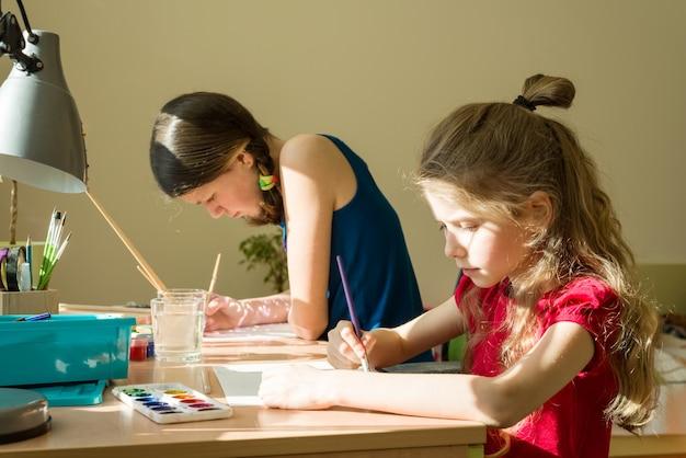Irmãs de meninas em casa na mesa pintar com aquarela