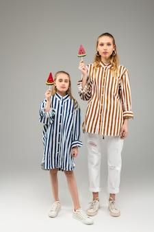 Irmãs decididas de cabelos claros usando roupas semelhantes enquanto ficam de pé com doces em um pedaço de madeira