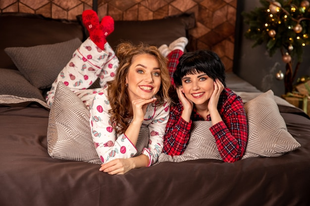 Irmãs deitadas na cama de pijama. eles sorrindo e celebrando a véspera de ano novo e o natal. existem presentes e ramos de abeto decorados com bolas douradas.