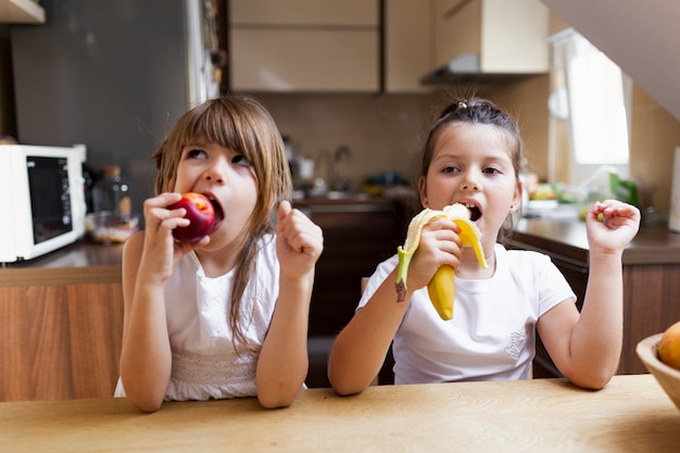 Irmãs do bebê que comem um lanche saudável