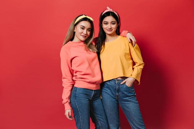 Irmãs em camisolas elegantes e faixas de cabelo posando na parede vermelha