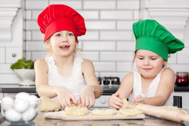 Irmãs em chapéus de cozinheiro brilhante assando juntos em uma cozinha