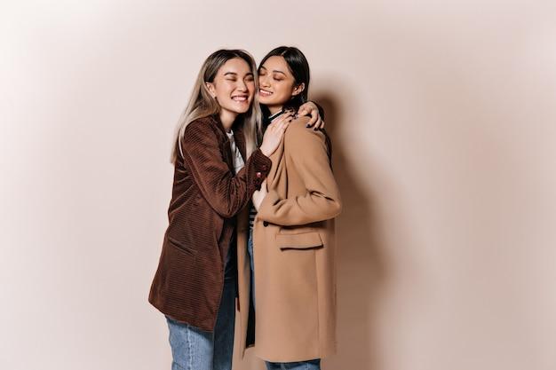 Irmãs em roupas elegantes posando em uma parede bege e se abraçando