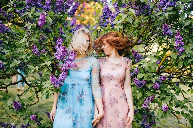 Irmãs felizes engraçadas, balançando a cabeça na árvore florescendo