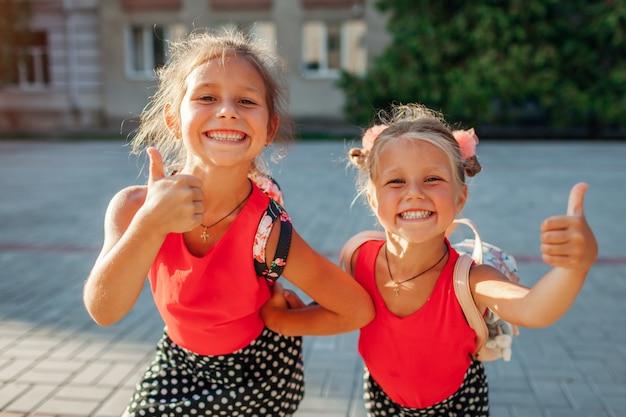 Irmãs felizes meninas vestindo mochilas e mostrando polegares para cima