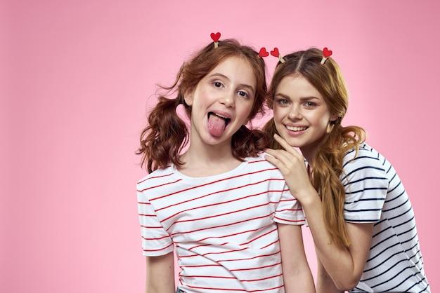 Irmãs felizes se divertindo em um fundo rosa e prendedores de roupa em forma de coração na cabeça