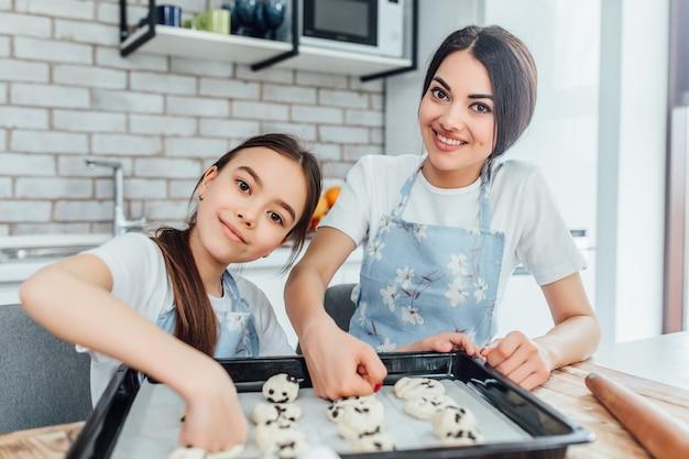 Irmãs garotas cozinham cupcakes na cozinha