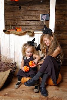 Irmãs garotas em fantasias de bruxa com decorações de halloween