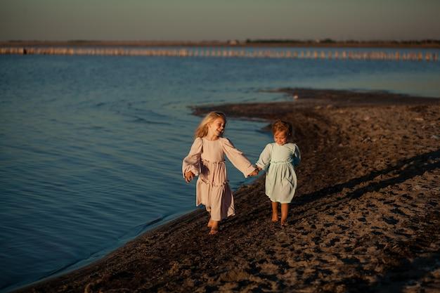 Irmãs gatas felizes correm ao longo da praia arenosa, verão e pôr do sol, meninas em vestidos e de mãos dadas