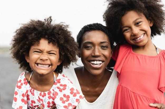 Irmãs gêmeas africanas se divertindo com a mãe na praia - foco no rosto da mulher