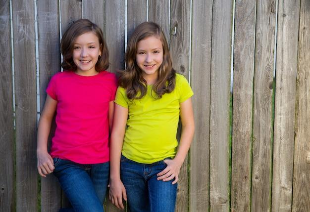 Irmãs gêmeas com penteado diferente posando na cerca de madeira