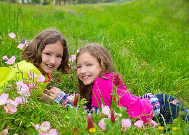 Irmãs gêmeas feliz meninas brincando na primavera flores prado
