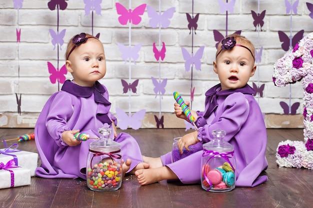 Irmãs gêmeas fofas comemorando seu primeiro aniversário