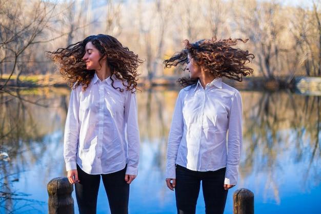 Irmãs gêmeas jovens na mesma roupa, sacudindo o cabelo no lago no dia de outono na floresta